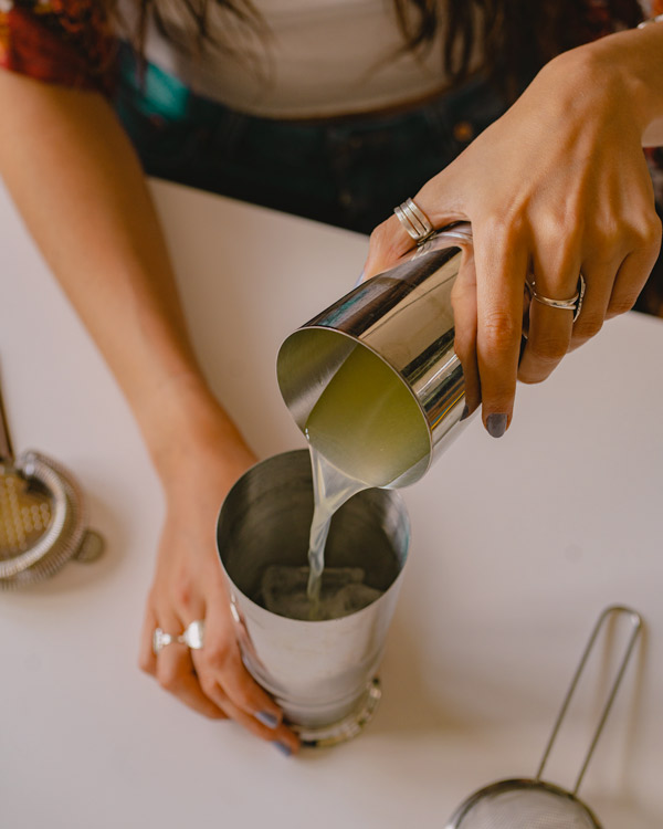 pouring the ingredients into a boston shaker