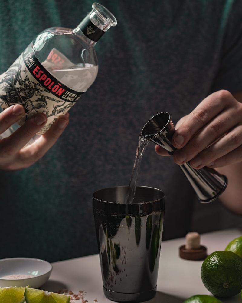 Pouring a jigger of espolon blanco tequila