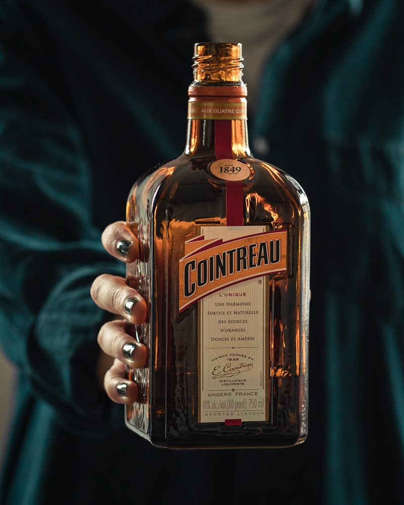 Holding a bottle of cointreau