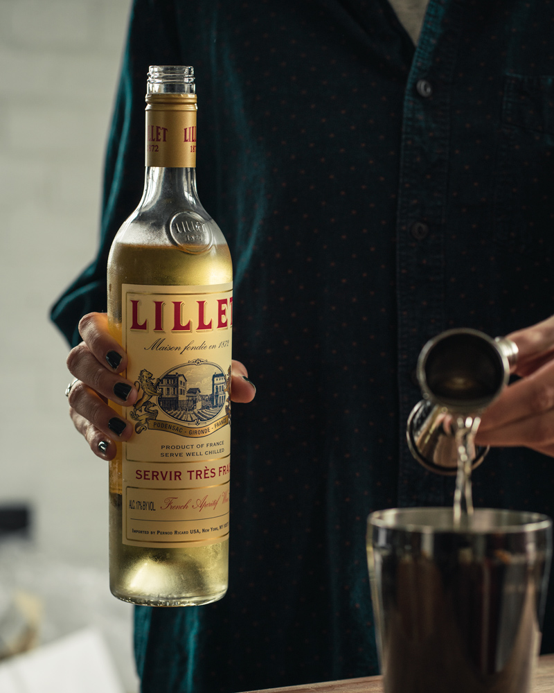Pouring a jigger of lillet blanc