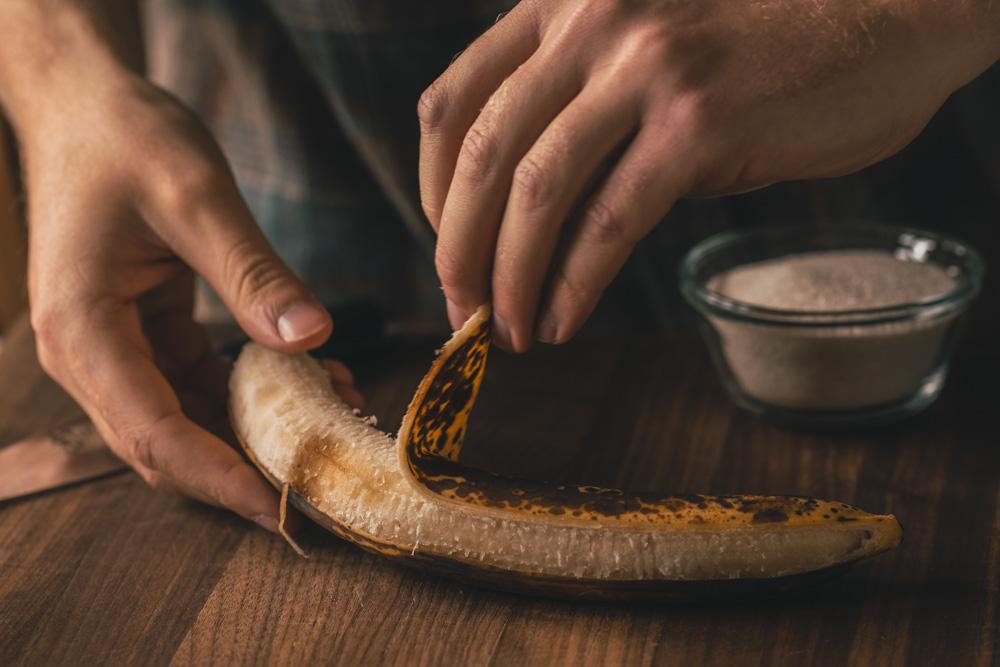 Peeling a banana to make homemade banana syrup
