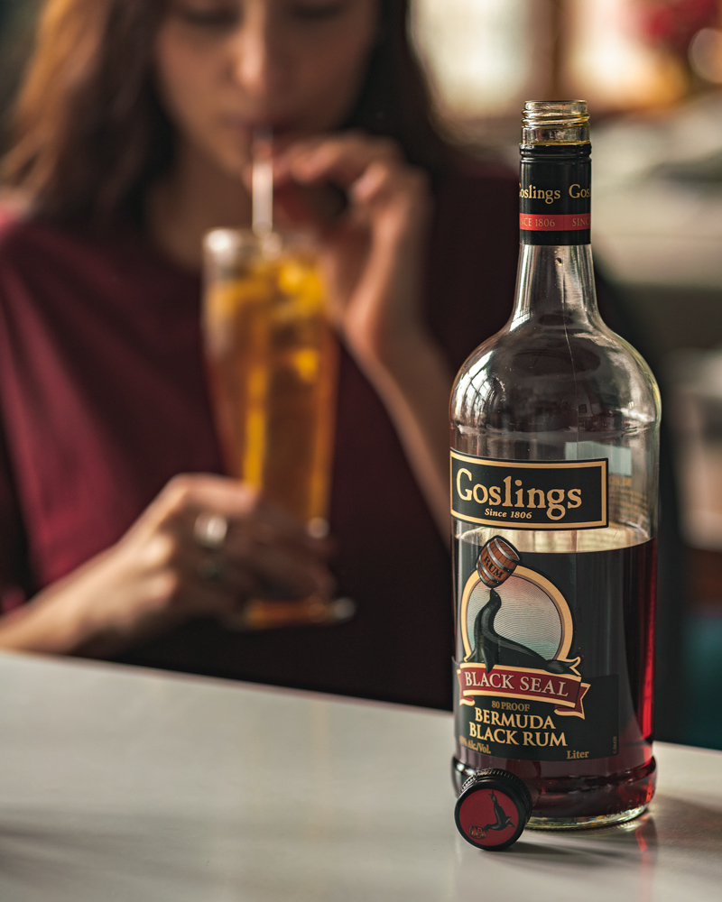 Bottle of Goslings rum and a girl drinking a dark and stormy