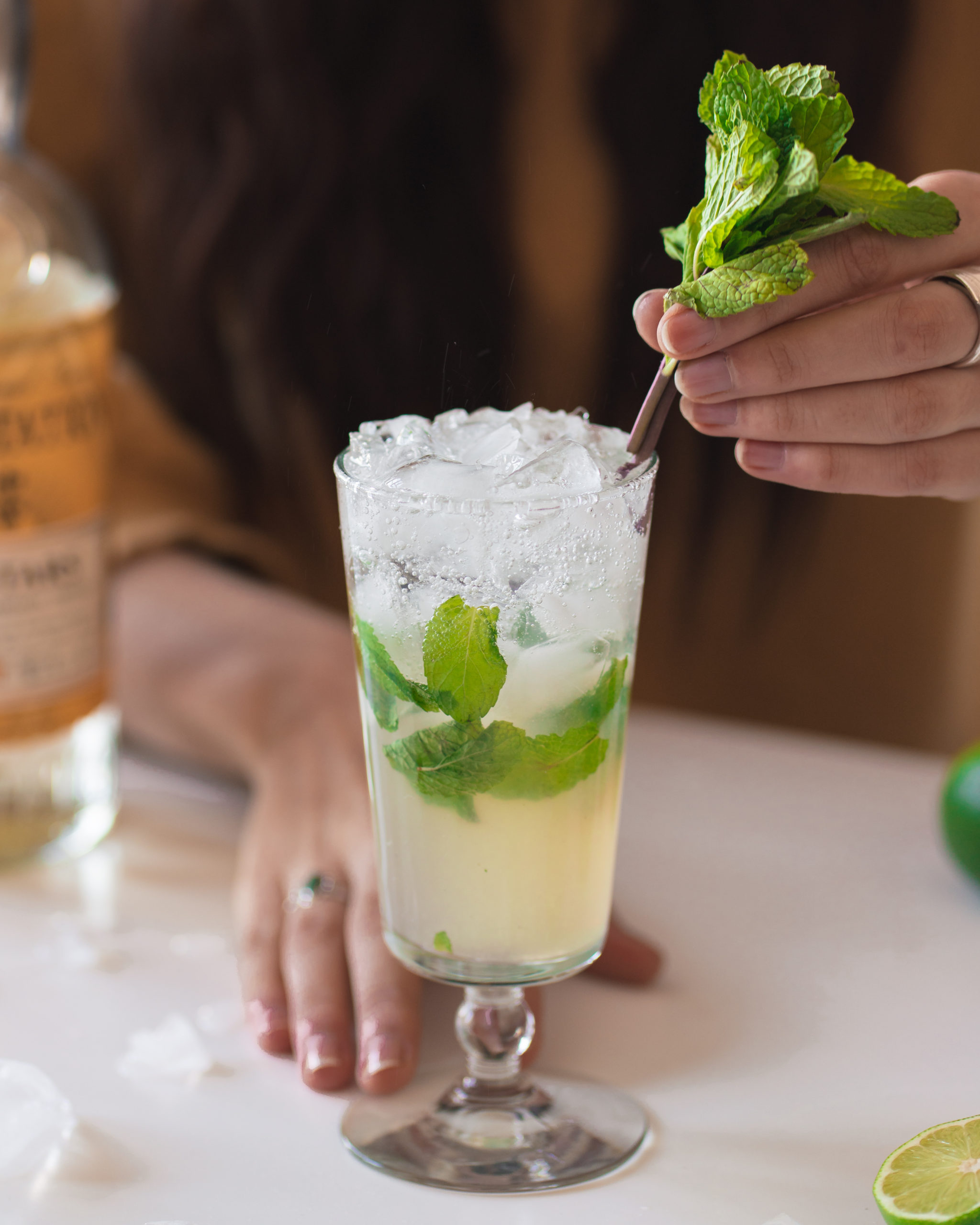 Garnihsing the finished mojito with a sprig of mint