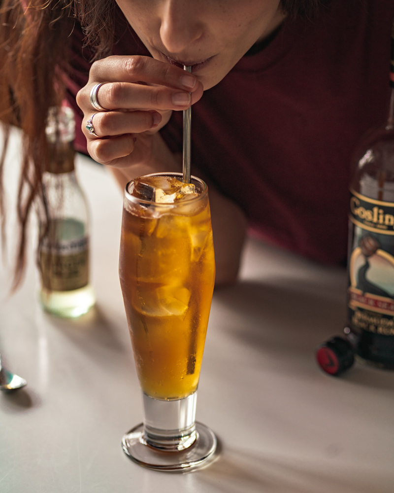 Taking a sip of a finished dark and stormy