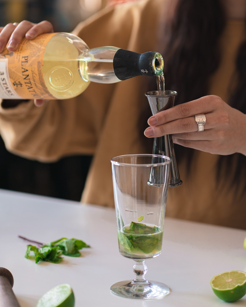 Pouring white rum into the mojito glass