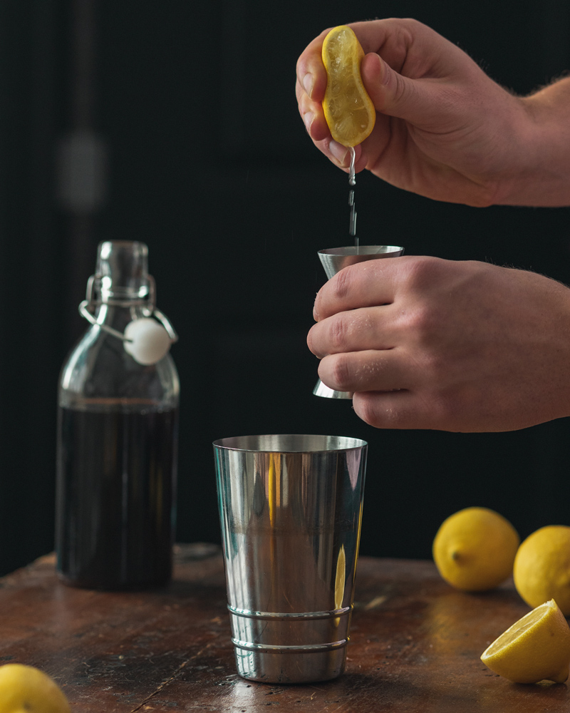 Squeezing fresh lemon juice for the scofflaw recipe