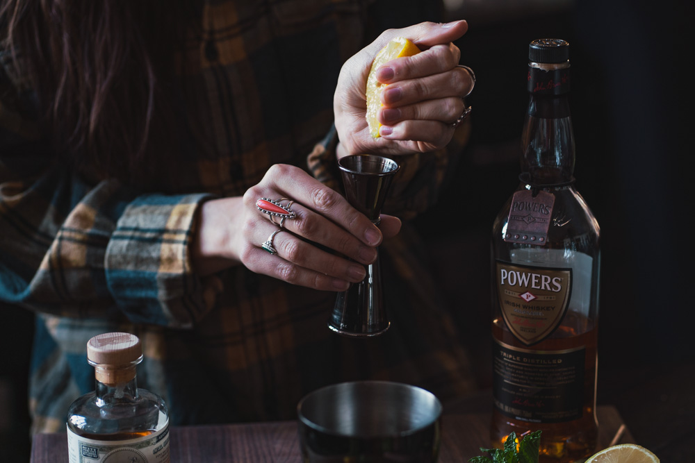 squeezing lemon for this Powers whisky cocktail
