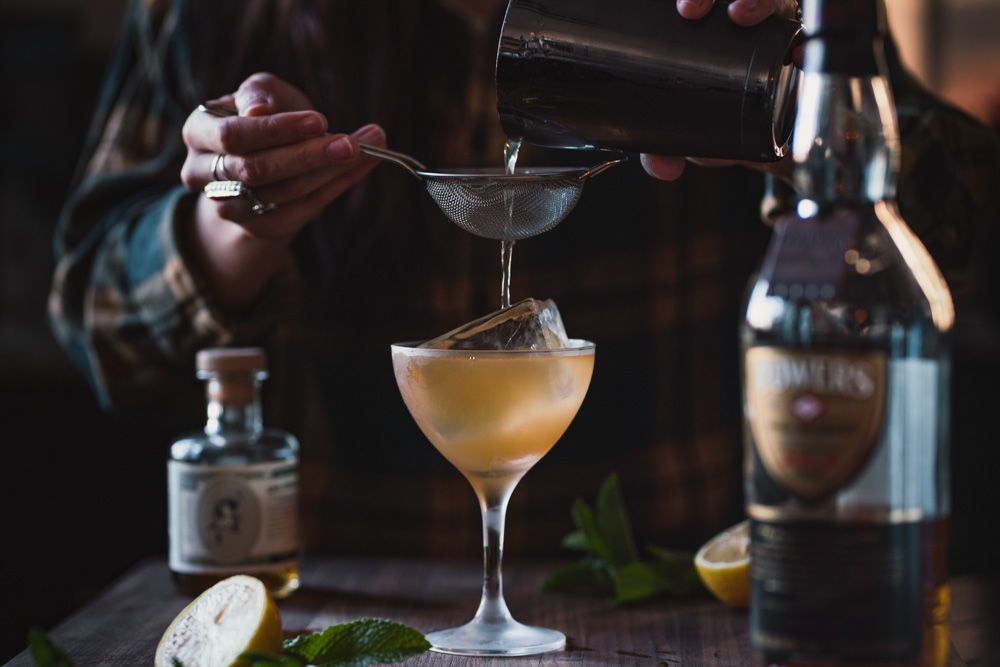 Straining this Powers Whisky cocktail