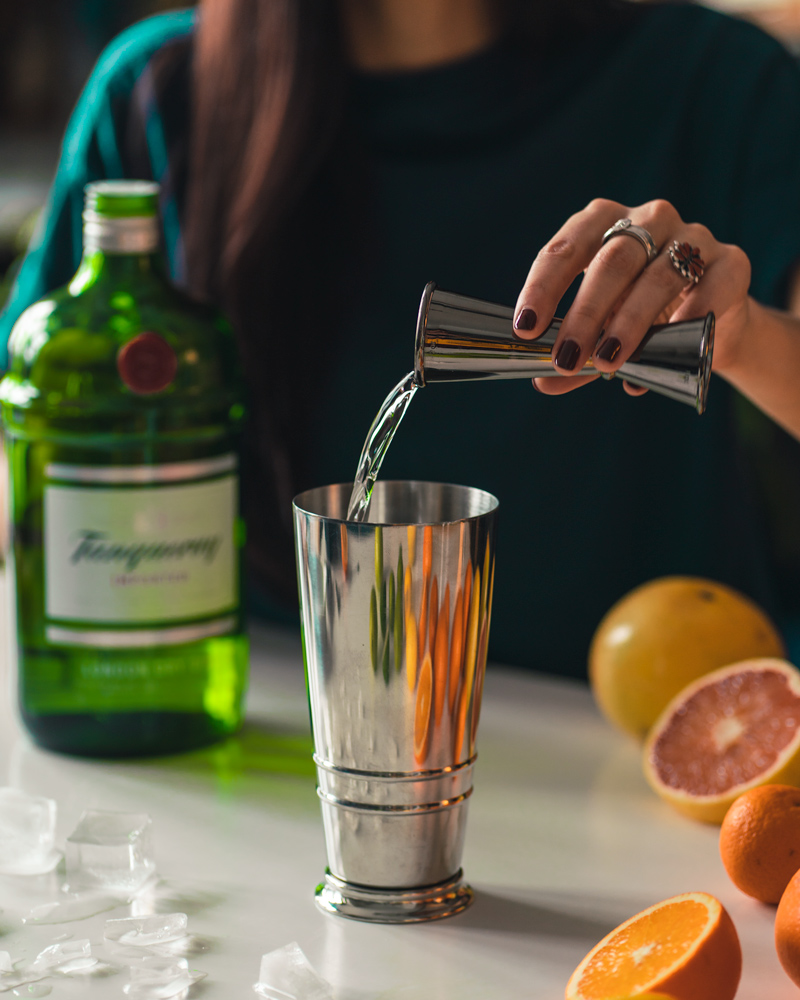 pouring tanqueray for a homemade gin and juice