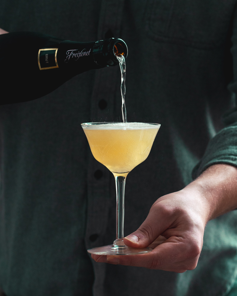 Pouring the Champagne into the final cocktail