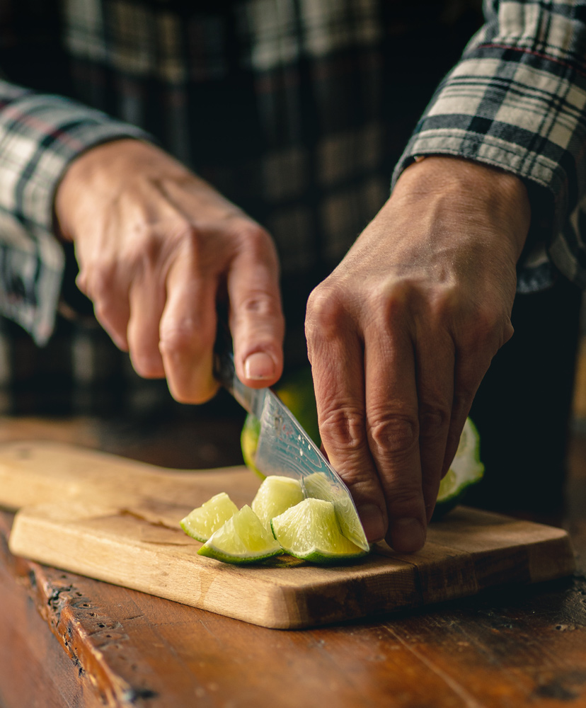 Cutting fresh limes to muddle in the caiprinha