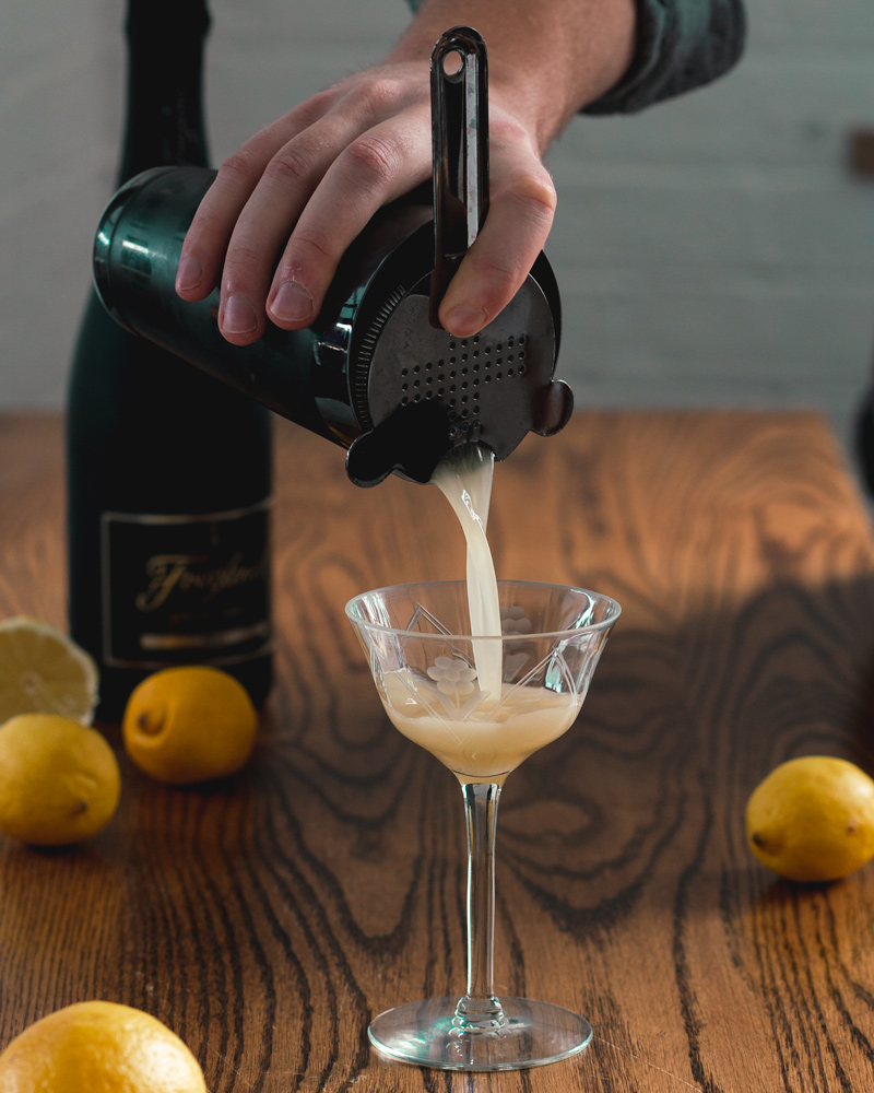 Straining the French 75 cocktail into a vintage glass