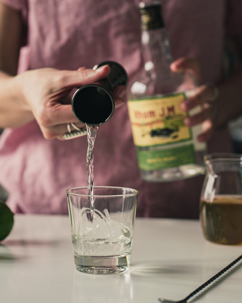 Pouring Rhum Agricole into the cocktail glass