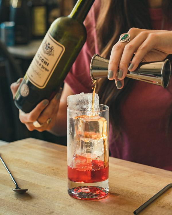 Pouring Cocchi vermouth into an Americano