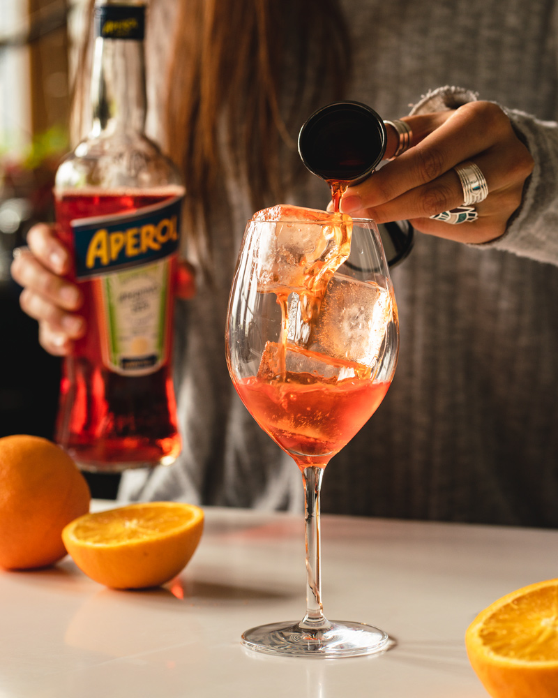 Pouring Aperol over ice in a wine glass