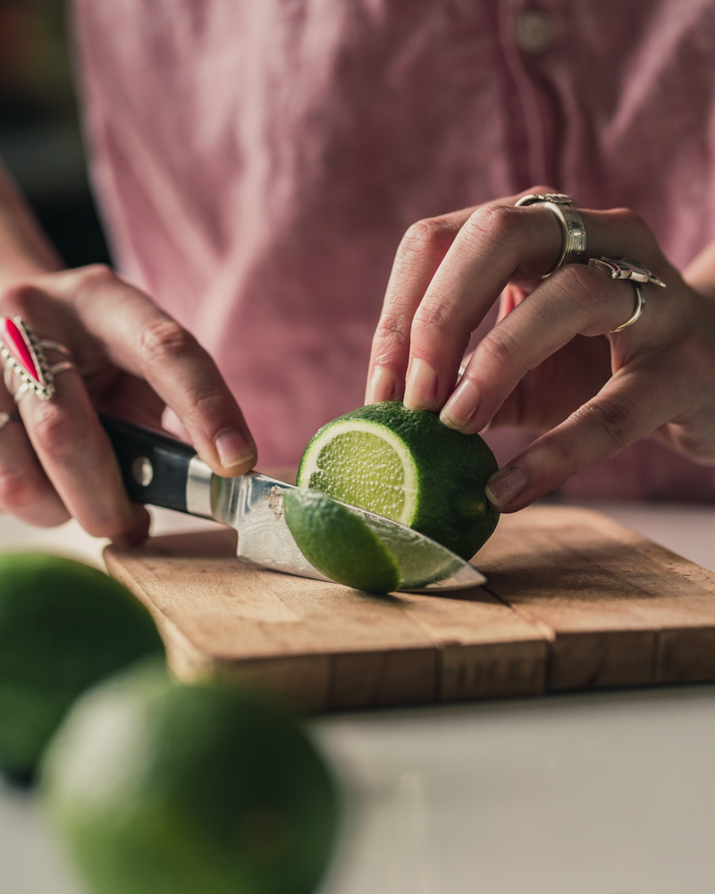 Slicing a disc of lime to use for the drink