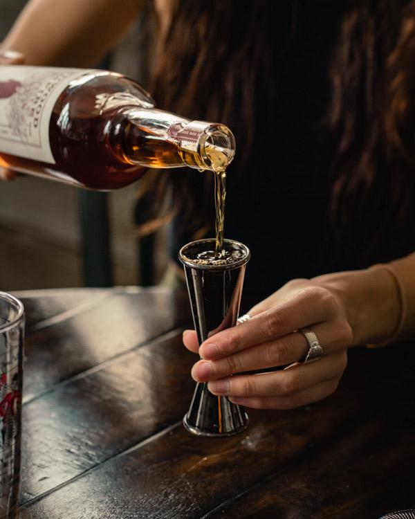 Measuring bourbon for the black manhattan