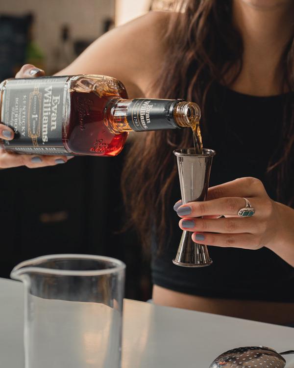 measuring bourbon for a manhattan