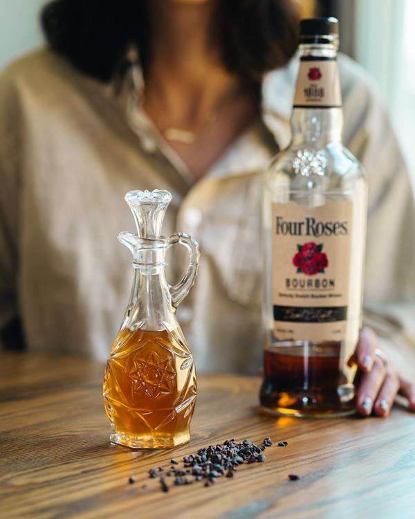 glass decanter with whiskey and cacao nibs